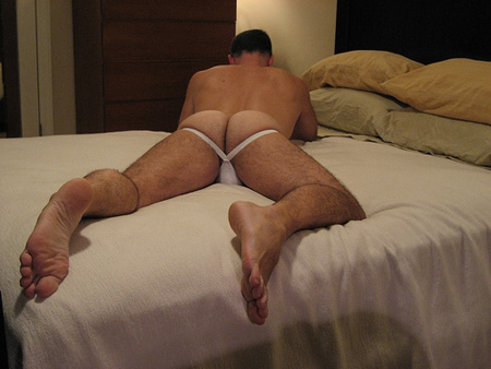 hot guy lying on the bed in nothing but a white jockstrap