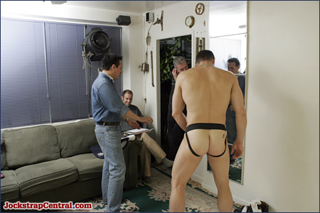 John and Ed look on as Peter arranges the bulge in his jockstrap