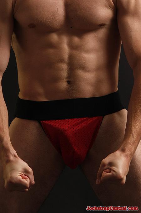 flexing in red sports mesh jockstrap